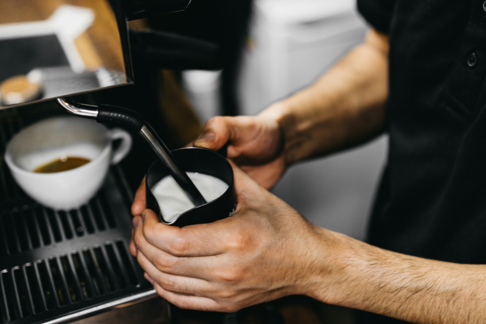 Milch wird für Cappuccino aufgeschäumt