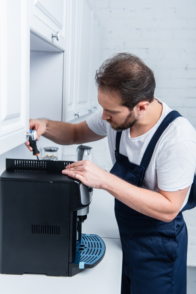 Fachmann repariert einen Kaffeevollautomaten